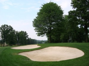 Two bunkers and a tree guard the landing area and the corner of the 16th.